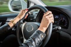 Las manos de la mujer en el volante del coche Fotografía de archivo
