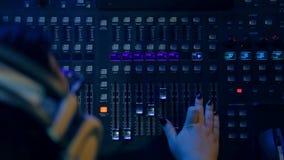 Las manos de la mujer en las pistas de mezcla de mezcla de una consola para el disco en la iluminación del color almacen de metraje de vídeo