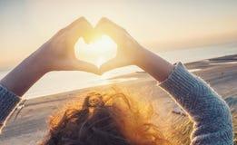 Las manos de la mujer en símbolo del corazón formaron con la luz de la puesta del sol en el beac imagen de archivo