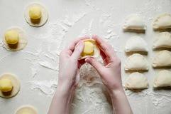 Las manos de la mujer esculpen las bolas de masa hervida con las patatas en el fondo blanco Alimento ucraniano tradicional imagen de archivo