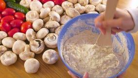 Las manos de la mujer están amasando la pasta de levadura con una espátula de madera en cuenco azul en la tabla con las verduras almacen de video