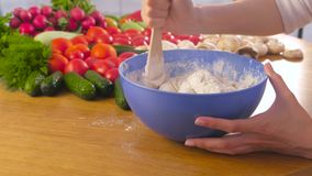 Las manos de la mujer están amasando la pasta de levadura con una espátula de madera en cuenco azul en la tabla con las verduras  almacen de metraje de vídeo