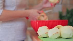 Las manos de la mujer están pelando la piel apagado de manzanas rojas usando un cuchillo almacen de video