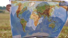 Las manos de la mujer están sosteniendo el mapa del mundo en el fondo del campo soleado La opinión del primer metrajes