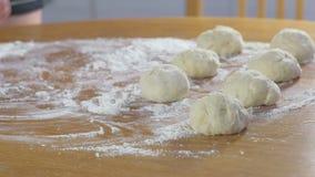 Las manos de la mujer hacen los bollos de la pasta de levadura en la tabla de cocina almacen de metraje de vídeo