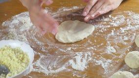 Las manos de la mujer hacen una empanada con arroz y el huevo de la pasta de levadura en la tabla de cocina almacen de metraje de vídeo