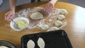 Las manos de la mujer hacen una empanada con arroz y el huevo de la pasta de levadura en la tabla de cocina metrajes