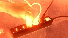 Las manos de la mujer insertan el interruptor de la extensión de los enchufes del alambre en piso de madera Visión que brilla int almacen de video
