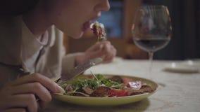 Las manos de la mujer joven que corta la carne fresca sabrosa que miente en la placa con el cierre vegetal para arriba Cena en metrajes