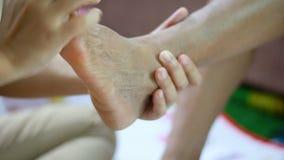Las manos de la mujer joven tocan suavemente masaje al pie de las mujeres mayores metáfora y concepto para la atención sanitaria  almacen de metraje de vídeo