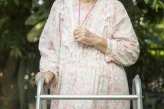 Las manos de la mujer mayor adentro ruegan con el caminante Fotos de archivo libres de regalías