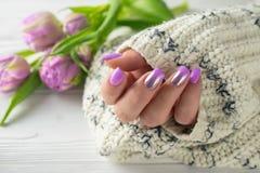 Las manos de la mujer preparada con el barniz de clavo púrpura, manicura, cuidado de la mano imagen de archivo