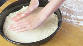 Las manos de la mujer pusieron la pasta de levadura en el molde para el horno redondo Fabricación de la pizza almacen de metraje de vídeo