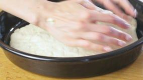 Las manos de la mujer pusieron la pasta de levadura en el molde para el horno redondo Fabricación de la pizza almacen de video