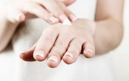 las manos de la mujer que aplican la crema imágenes de archivo libres de regalías
