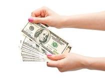 Las manos de la mujer que cuentan 100 billetes de banco del dólar de EE. UU. Fotografía de archivo libre de regalías