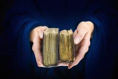 Las manos de la mujer que dan dos libros viejos Fotos de archivo libres de regalías
