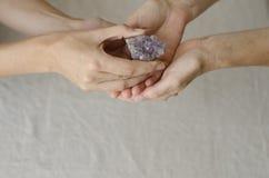 Las manos de la mujer que dan un cristal uno de la amatista a otro Imagenes de archivo