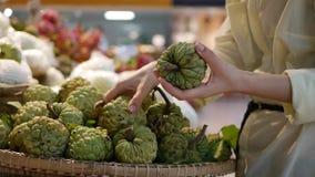 Las manos de la mujer que eligen la anona o la manzana del azúcar en el supermercado metrajes