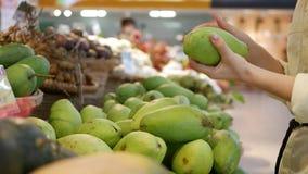 Las manos de la mujer que eligen los mangos frescos en el supermercado metrajes