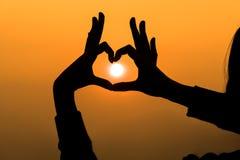 Las manos de la mujer que forman un corazón forman con la silueta de la puesta del sol foto de archivo libre de regalías