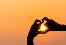Las manos de la mujer que forman un corazón forman con la silueta de la puesta del sol Imagenes de archivo