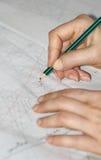 Las manos de la mujer que remontan el dibujo de costura Foto de archivo libre de regalías