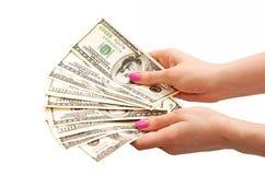 Las manos de la mujer que sostienen 100 billetes de banco del dólar de EE. UU. Fotografía de archivo