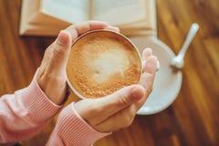 Las manos de la mujer que sostienen el café en el café Imagen de archivo