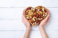 Las manos de la mujer que sostienen el cuenco en forma de corazón con las nueces mezcladas en la opinión de sobremesa blanca Comi imagen de archivo
