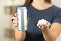 Las manos de la mujer que sostienen una bebida de la soda pueden y los cubos del azúcar foto de archivo libre de regalías