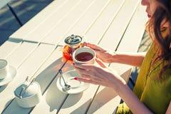 Las manos de la mujer que sostienen una taza de té imagenes de archivo