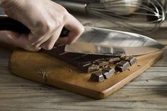 Las manos de la mujer que tajan la barra de chocolate con el cuchillo foto de archivo libre de regalías