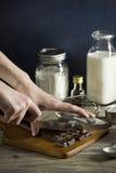 Las manos de la mujer que tajan la barra de chocolate con el cuchillo fotos de archivo libres de regalías