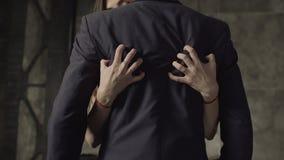 Las manos de la mujer que tapan clavos en la parte posterior del socio metrajes