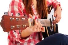 Las manos de la mujer que tocan la guitarra acústica, cierre para arriba fotos de archivo