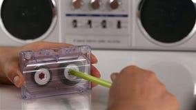 Las manos de la mujer rebobinan un casete audio usando una pluma