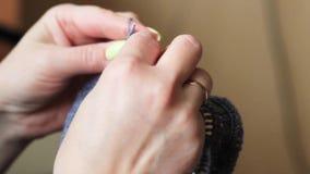 Las manos de la mujer se cierran encima de hacer punto Hilado gris y agujas finas metrajes