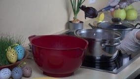 Las manos de la mujer toman los huevos envueltos en el material del agua de ebullición del pote con la pintura metrajes