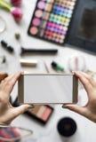 Las manos de la mujer usando la foto de la captura del teléfono móvil con los cosméticos apoyan Fotografía de archivo