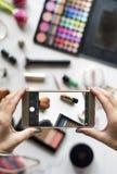 Las manos de la mujer usando la foto de la captura del teléfono móvil con los cosméticos apoyan Fotografía de archivo libre de regalías