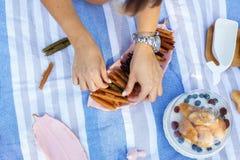 Las manos de la mujer de la visión superior toman el rollo del pastillum de la bandeja Comida campestre del verano fotografía de archivo