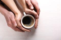 Las manos de la mujer y del hombre que agujerean la taza de café Fotografía de archivo