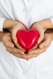 Las manos de la mujer y del hombre que llevan a cabo el corazón rojo junto imagen de archivo libre de regalías