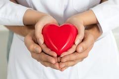 Las manos de la mujer y del hombre que llevan a cabo el corazón rojo junto foto de archivo