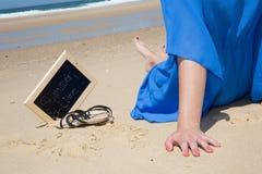 Las manos de la mujer y pierna con la pizarra y tiempo de verano en ella contra el mar Fotografía de archivo libre de regalías
