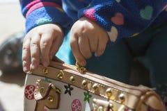 Las manos de la niña abren una cartera Imagen de archivo libre de regalías