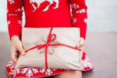 Las manos de la niña están sosteniendo el regalo de la Navidad imagen de archivo libre de regalías