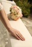 Las manos de la novia con el anillo de bodas y el ramo de flores Fotos de archivo libres de regalías