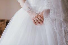 Las manos de la novia en el vestido blanco, alistan para la ceremonia de boda, Imagenes de archivo